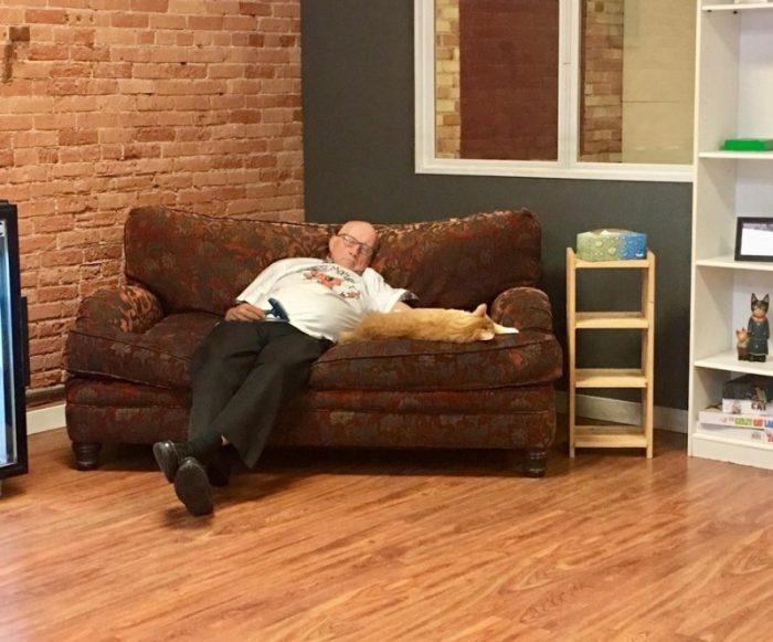Мужчина на диване с кошкой