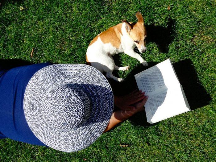 Девушка читает рядом с собакой