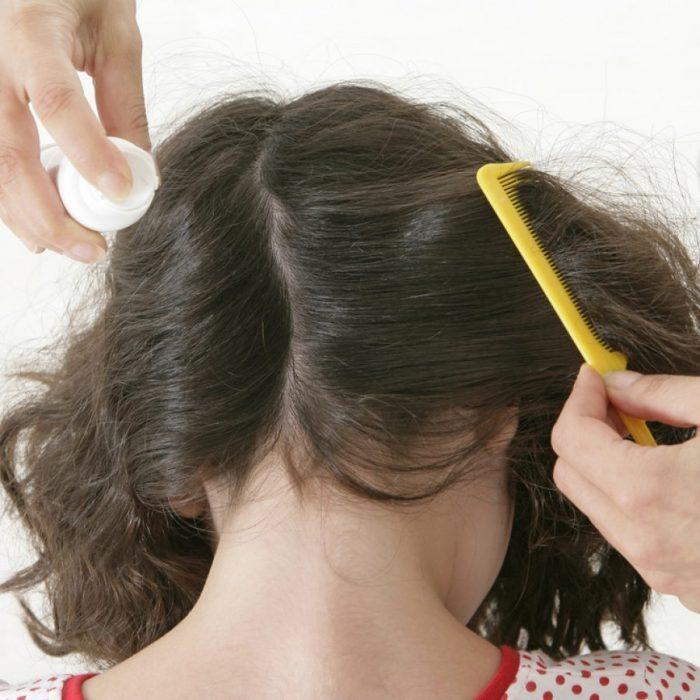 Девочке обрабатывают волосы средством от вшей