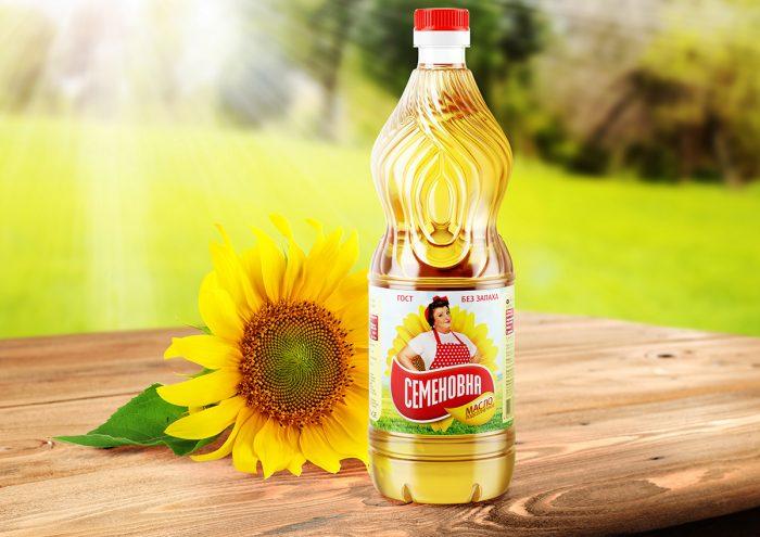 Подсолнечник и бутылка с растительным маслом на столе
