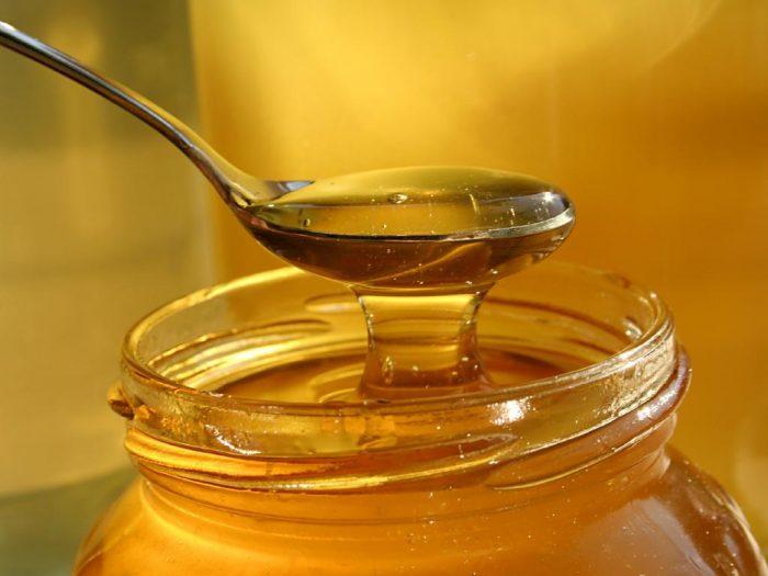 Мёд набирают ложкой из банки