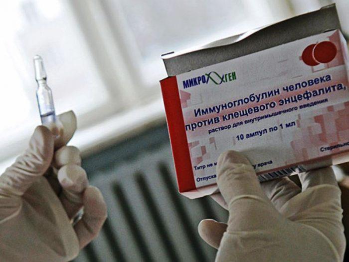 Ампула с противоэнцефалитным иммуноглобулином и коробка от него в руках