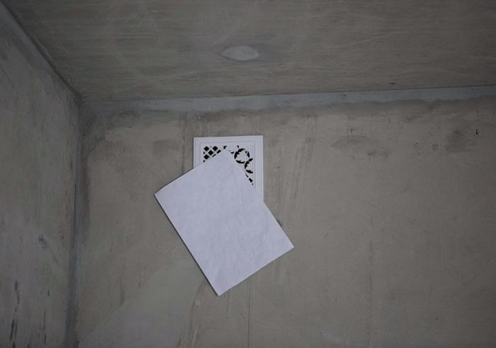 Лист бумаги у вентиляционной решётки в комнате