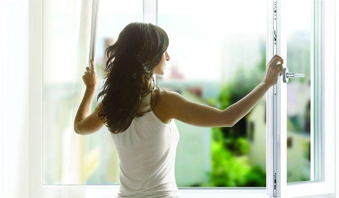 Девушка в белой майке открывает окно