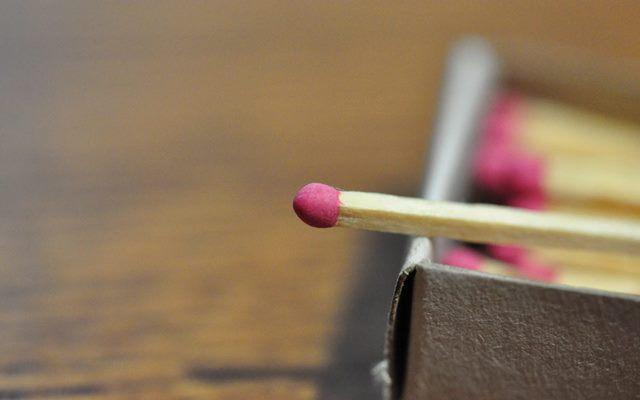 Спичка с розовой серной головкой на коробке