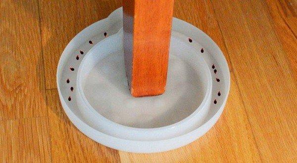 деревянная ножка мебели стоит в крышке с водой