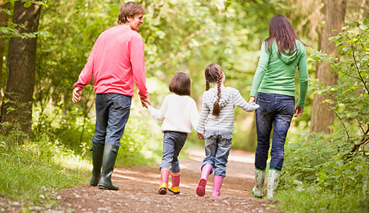 Папа в розовом свитере, мама в зелёной кофте и две дочки на прогулке в парке, вид со спины