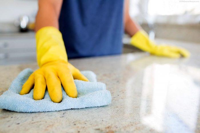 Тряпкой моют пол в резиновых перчатках