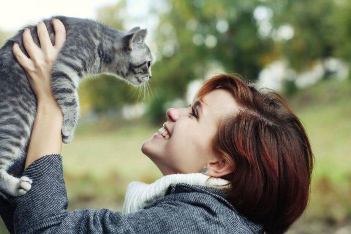 Женщина обнимает кота