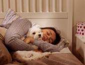 Женщина спит в обнимку с болонкой